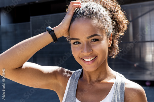 Beautiful sporty woman holding her hair, resting after daily workout Tablou Canvas