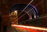 Fototapeta Londyn - Most Tower Bridge w Londynie, nocą, kolorowo podświetlony, smugi świetlne od poruszających się pojazdów, długi czas naświetlania