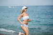 Beautiful young blonde woman in white sportswear is running on beach