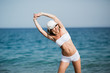 Slim female girl with beautiful figure is doing stretching exercise on the beach, morning run, fitness and healthy lifestyle concept