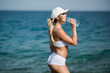 Beautiful fitness athlete woman drinking water after work out exercising on the beach outdoor portrait
