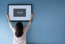 New Year Concept. Asian Woman Holding A Picture Frame Of 2018 On Blue Wall.