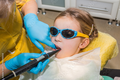 kid in dentist clinic Dental health  Female dentist curing a child