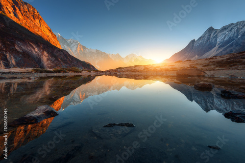 Fotografia  Wonderful landscape with high rocks with illuminated peaks, stones in mountain lake, reflection, blue sky and yellow sunlight in sunrise