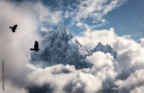 Foto auf Leinwand Gebirge Two flying birds against majestical Manaslu mountain with snowy peak in clouds in sunny bright day in Nepal. Landscape with beautiful high rocks and blue cloudy sky. Nature background. Fairy scene