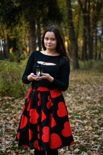 Fotografía  Romantic elegance pretty young girl holding candlestick while walking cold eveni