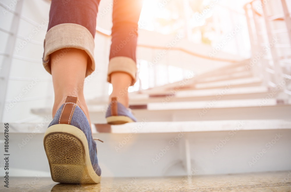 Fototapeta Young adult woman walking up the stairs with sun sport background.