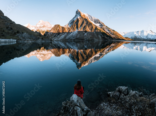 Papiers peints Statue Young adult woman wearing red jacket enjoying the view over a mirror-like mountain lake in the Austrian Alps during sunset