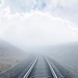 zbliżenie kolejowe idzie do horyzontu we mgle pod zachmurzonym niebie - 180675458