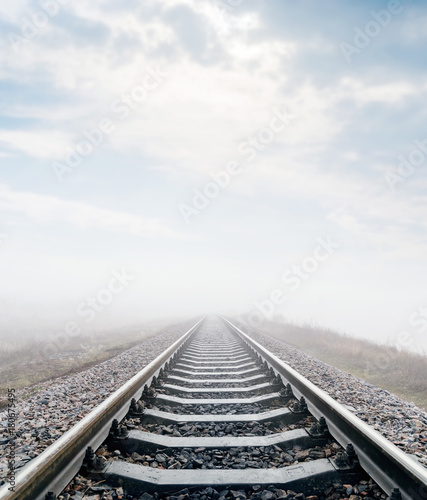 railroad in meadow with fog and clouds over it