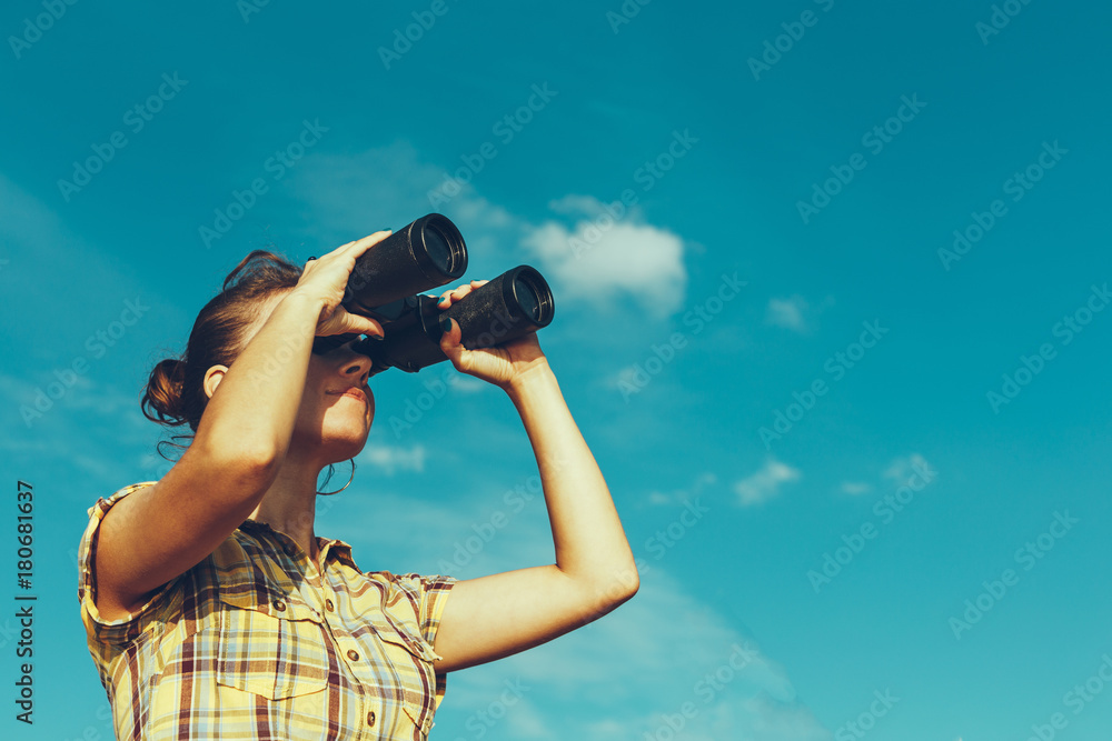 Fototapety, obrazy: Beautiful Young Girl Looking Through Binoculars On Blue Sky Background. Travel Holidays Journey Concept