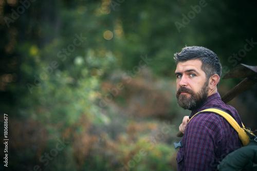 Fototapeta Man hiker hold axe and backpack on summer day obraz