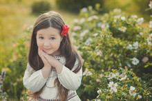 Girl With Brunette Hair And Brown Eyes Stylish Dressed Wearing Rustic Village Clothes White Shirt And Red Pants On Belt Posing With Flowers In Forest Meadow