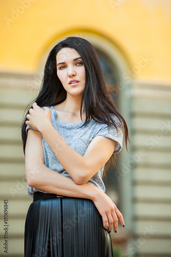 20508c8fba cute young girl posing near building. sweet woman in a gray T-shirt and a  black leather skirt walking around city. Concept of modern freedom hipster  human