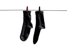 Black Socks Hang Drying On The Clothesline With Clothespins. Closeup. Isolated On A White Background