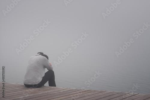 Junge Frau sitzt einsam am Rand eines Weges gebückt und traurig mit dem Kopf in den Armen versteckt Rückansicht
