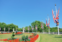 LONDON, ENGLAND - AUGUST 01, 2013: Park With Green Grass And Bright Red Flowers On Flowerbed Near Flags Of United Kingdom Near Buckingham Palace.