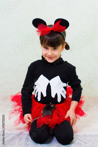Photo  cute little girl in a bear costume with ears holds a hand rat