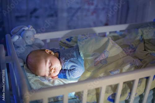 Adorable newborn baby boy, sleeping in crib at night Wallpaper Mural