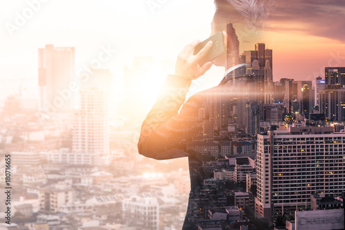Fotografia  The double exposure image of the business man using a smartphone calling during sunrise overlay with cityscape image