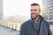 Leinwanddruck Bild - Happy man standing outdoors during sunny winter day