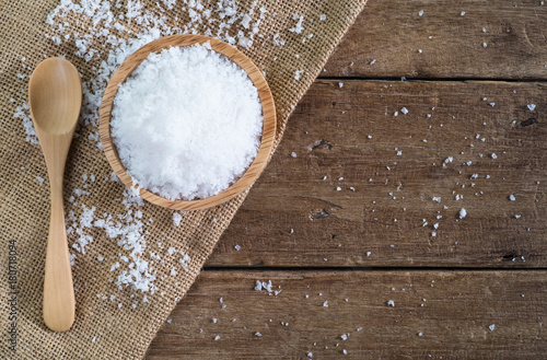 white sea salt in wood bowl with wood spoon on gunny sack cloth on brown wooden table, top view with copy space