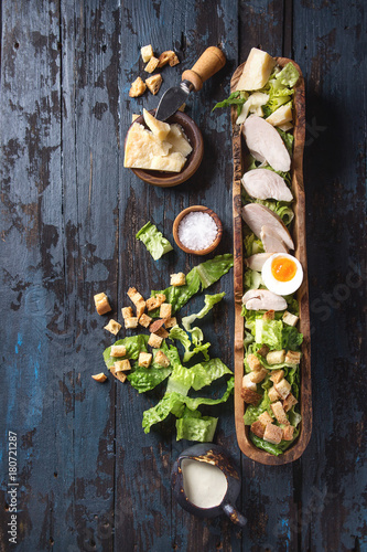 Photo  Classic Caesar salad with grilled chicken breast and half of egg in olive wood bowl