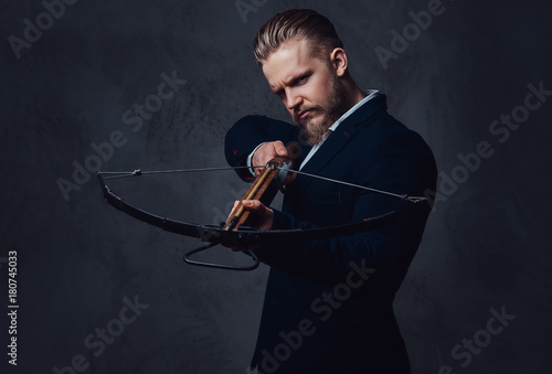 Canvas A man dressed in a suit holds crossbow.