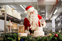 Santa Claus A Confectioner Cooks A Cake In The Kitchen On Christmas Day.