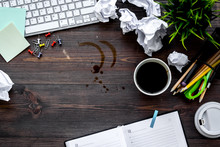 Clutter In Office. Desk Covered With Crumpled Paper And Coffee Stains. Dark Wooden Background Top View Copyspace