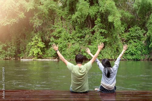 Photo  Happy couple hands up and sitting near river