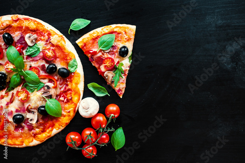 Pizza slice with Pepperoni, melting cheese and olives served at a pizzeria or restaurant
