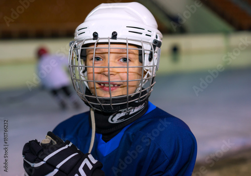 A boy plays hockey on the ice area. Boy seven years.