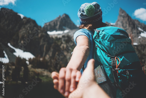 Fotografiet Young active hiking couple with backpacks taking photo, woman guiding by the han