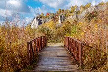 Beautiful Autumn Fall View Of Canadian Ontario Park Scarborough Bluffs With Cliffs On Background. Small Bridge Leading To Pathway In Bushes, Grass. Sunny Day With Blue Sky And Clouds Outside