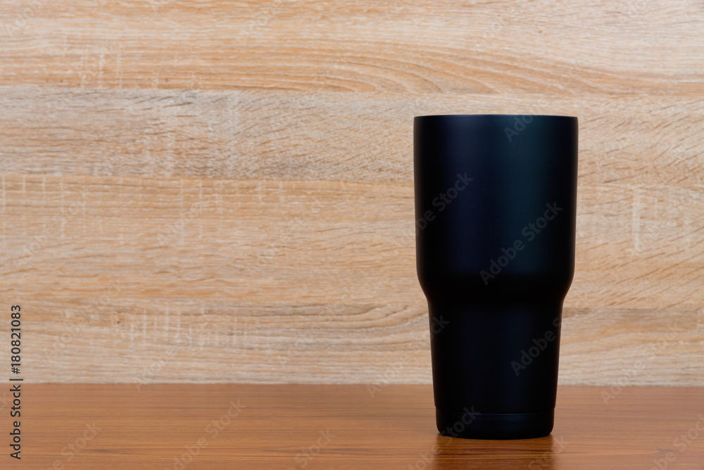 Fototapeta Black colour stainless steel tumbler or cold storage cup on wood background.