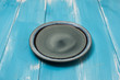 Round plate on blue wooden table with perspective