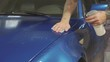 Close up of master polishing deep blue car in workshop, slow motion
