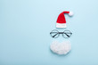 Leinwanddruck Bild - Creative christmas composition. Greeting card, invitation or flyer. Santa hat, beard and glasses on blue background top view. Flat lay.
