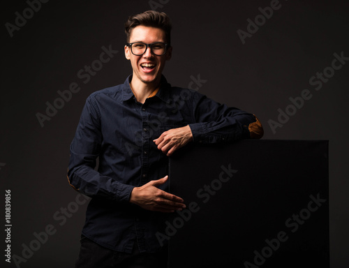 Fototapeta Young happy man portrait of a confident businessman showing presentation, pointing paper placard black background. Ideal for banners, registration forms, presentation, landings, presenting concept. obraz na płótnie