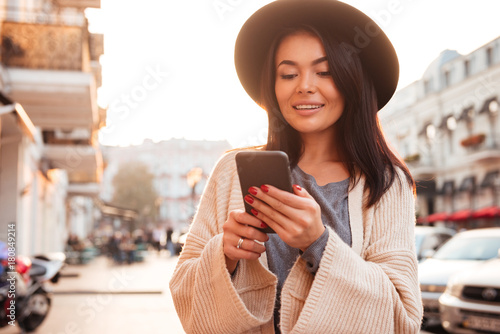 Fotografía  Stylish asian woman in black hat texting message on mobile phone while walking o