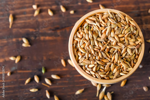 Foto Barley grain in wooden bowl on wooden table