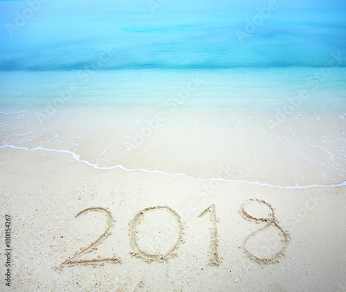 happy new year 2018 lettering on the beach with wave and clear blue sea numbers 2018 year on the sea shore message written in the white sand on the