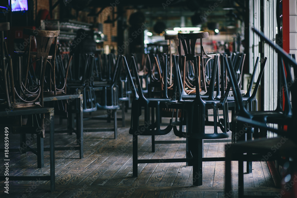 Fototapeta Chairs and tables stacked in a closed pub
