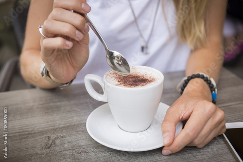 Close-up of woman with cappuccino in a street cafe
