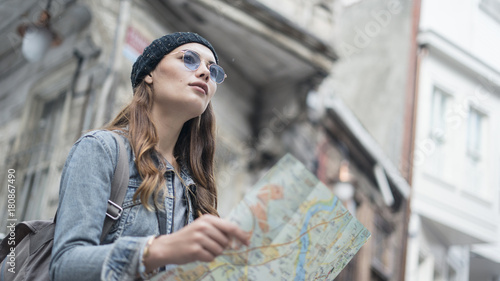 Fototapeta  Young tourist woman hand map in outdoors