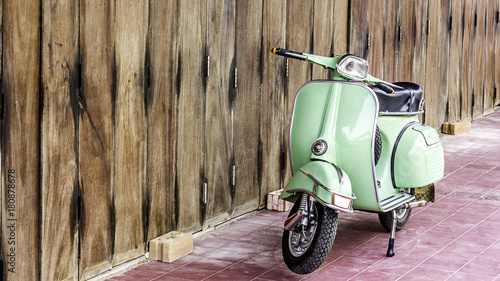 Spoed Foto op Canvas Scooter Green scooter against old house. wood wall mossy surface of building as background. Urban street in Thailand, Asia. Moped parked at moldy wood wall. Asian lifestyle and popular transport.