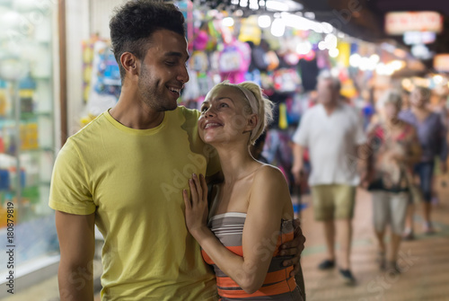 Foto op Plexiglas Caraïben Couple Embracing On Street Market, Mix Race Man And Woman Happy Smiling Looking At Each Other Shopping