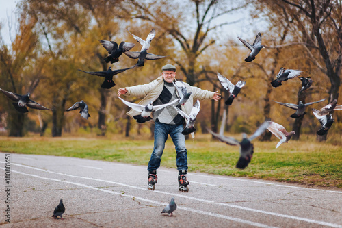 An elderly man has fun skating on roller skates. The man is spreading hands. People and pigeons.