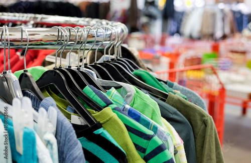 Foto op Plexiglas Dragen Kleiderständer mit einer Auswahl bunter Kleidung - selektive Schärfe und viel Copyspace